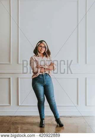 Empowering woman standing by a white wall