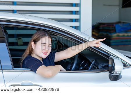A Young Woman Sitting In A Private Car Pointing Forward, Giving Directions.
