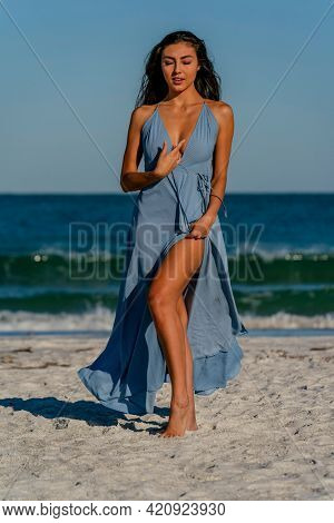 A beautiful mixed race bikini model enjoys the weather outdoors on the beach