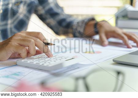 Businessman Hand Working With Finances About Cost And Calculator On White Desk In Office. Businessma