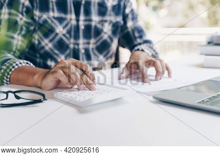 Businessman Using Calculator And Laptop Computer For Calculating With Finance Paper, Tax, Accounting