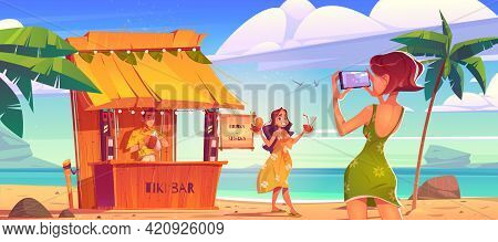 Woman Posing On Beach For Photo Shoot With Cocktails In Hands Near Tiki Hut Bar With Barman. Young G