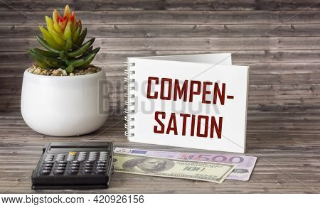 The Word Compensation Is Written On A Notepad. Euro And Dollar Banknotes, Calculator And Cactus Lie