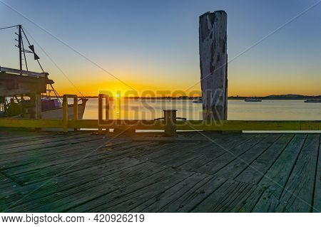 Into The Sunrise At Tauranga Waterfront Wharf Back-lit By Sun On Distant Horizon, Bay Of Plenty New