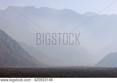 Haze Surrounding Rugged Mountainous Terrain With Alpine Mountain Peaks Beyond Taken From The Rural C