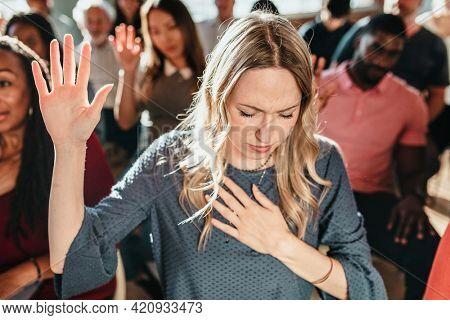 White woman raising her hand