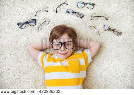 Happy Handsome Child Boy Trying On Glasses. Health, Medicine And Ophthalmology Concept