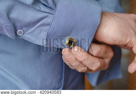 Close-up Of Hands Buttoning A Cufflink On The Sleeve Of A Blue Shirt. A Middle-aged Adult Man With A