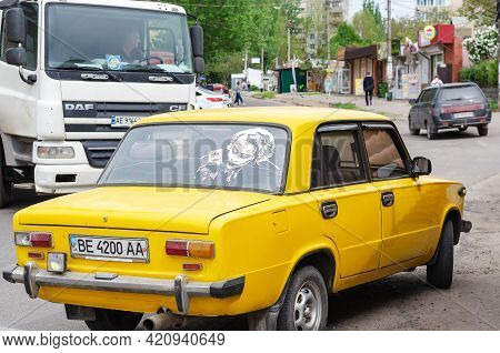 Rear View Of The Yellow Sedan With The Joker Pattern On The Rear Window. The Car Is Standing On A St