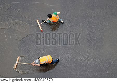 Two Workers Cleans The Street After The Rain. Janitors With Brushes Washes Wet City Road, View From