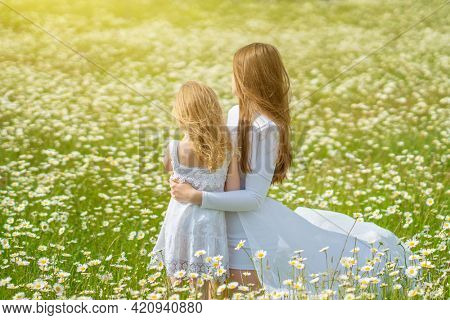 Mother and daughter in big camomile meadow. Emotional, love and care scene.