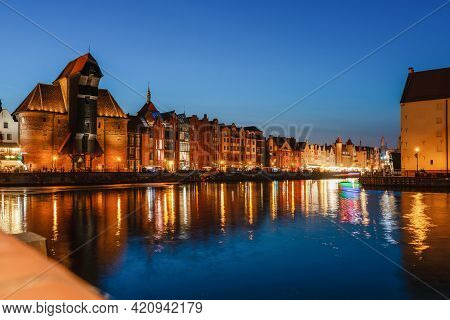 Gdansk Night City Riverside View. View On Famous Crane And Facades Of Old Medieval Houses On The Pro