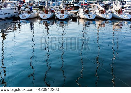 Sailing Yachts Moored On A Pier In A Harbour On Baltic Sea In A Sunny Morning, View On Back Decks An