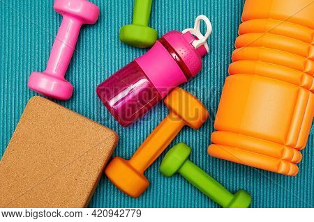 Flat Lay With Scattered Dumbbells, Fitness Bricks And Bottle On The Sports Mat. Bodycare And Healthc