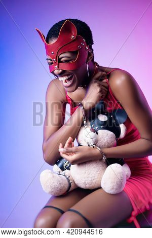 Black Woman In A Bdsm Cat Mask Laughs Handcuffed With A Teddy Bear In Her Hands