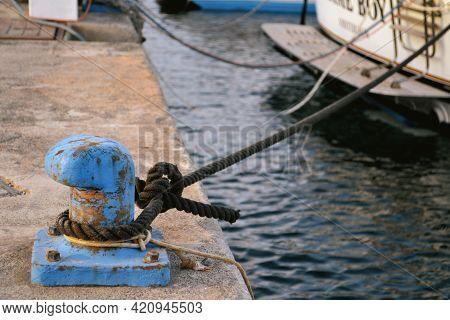 Rusty Blue Mooring Bollard With Ship Ropes