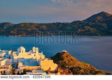 View of Plaka village on Milos island with traditional greek white houses with Greek Orthodox christian churck on sunset. Plaka town, Milos island, Greece