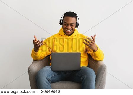 Black Millennial Guy Chatting Online Using Laptop On Gray Background