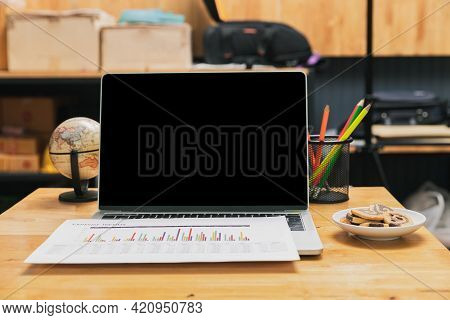 Laptop With Blank Screen, Report, Cookies With Globe And Pencils On Desk In Home Office.