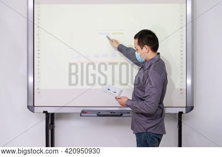 Businessman Wearing Protective Masks Present The Monthly College Budget In Front Of Tv To His Collea