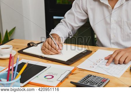 Businessman Take A Note On Notebook With Documents In Home Office.