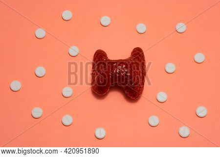 Thyroid Gland Concept Art Photo. The Thyroid Gland Is On A Beige Background Surrounded By White Pill