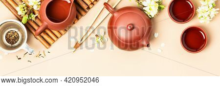 Asian Tea set on stone slate board, ceramic teapot, cups, dried tea and spring branches, tea ceremony , flat lay, copy space
