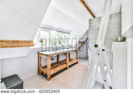 Wooden Table With Sinks Located Near Windows In Stylish Light Attic Restroom At Home