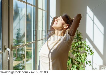 Enjoying New Day. Beautiful Happy Mature Woman Stretching Body And Smiling While Standing With Close