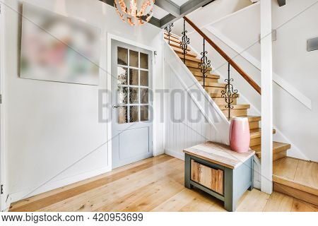 Stylish Decorations Located Near Door And Stairway With Ornamental Banister In Hallway Of House