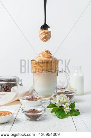 Dalgona Coffee And A Spoon With Coffee Foam Over A Glass On A White Background. Korean Invigorating