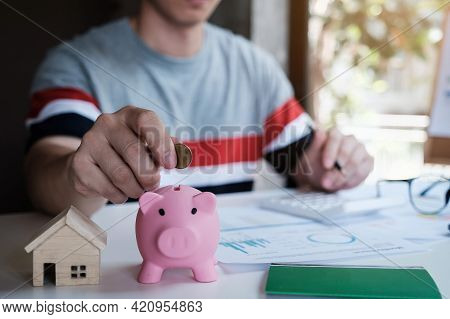 A Person Inserting Coin In Piggybank. Investment Asset Real Estate Property Concept.