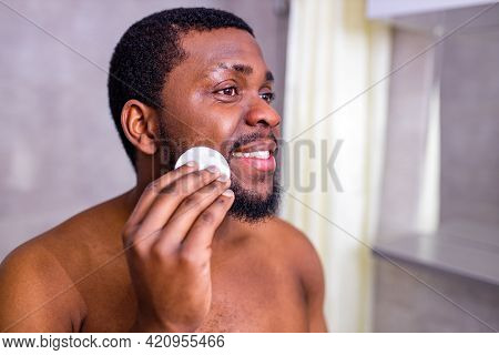 African American Man Looking At Himself In The Bathroom Mirror Squeezing Pimple