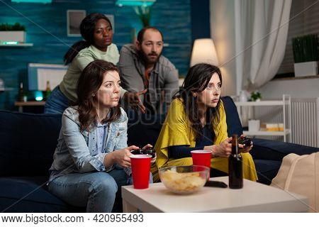 Group Multi-ethnic Friends Playing Videogames Using Controller During Online Battle Competition. Peo