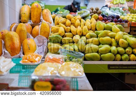 Fresh Papayas, Mangoes, And Colorful Fruit In Stand
