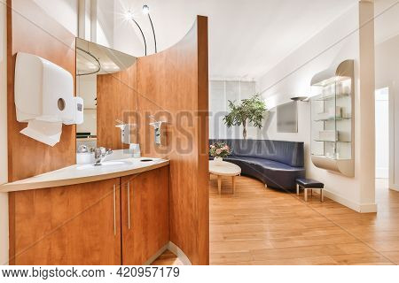 Sink With Mirror And Toiletries Located In Front Of Partition In Lobby Of Modern Office
