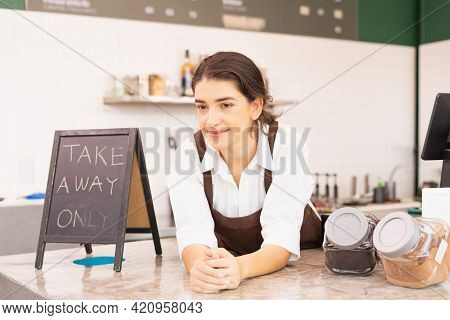 Beautiful Caucasian Barista Woman Place Hands-on Table Of Coffee Bar Near Takeaway Sign And Coffee B