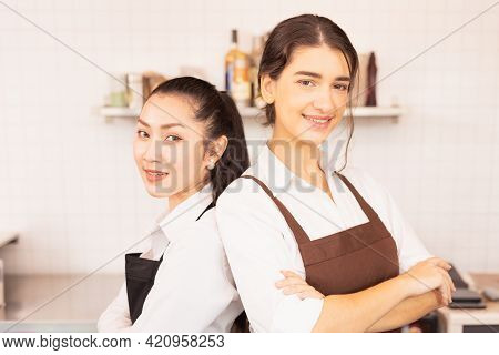 Close-up Beautiful Caucasian And Asian Barista Women Stand With Crossed Arms To Welcome Customers At