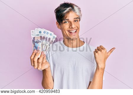 Young hispanic man holding russian 500 ruble banknotes pointing thumb up to the side smiling happy with open mouth