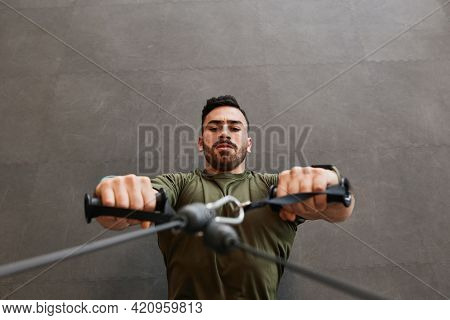 Handsome Muscular Bearded Fitness Guy Training His Chest By Doing Weighted Cable Crossover Exercise.