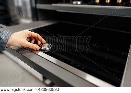 Close Up Of A Woman Hand Checking New Stove In A Hypermarket