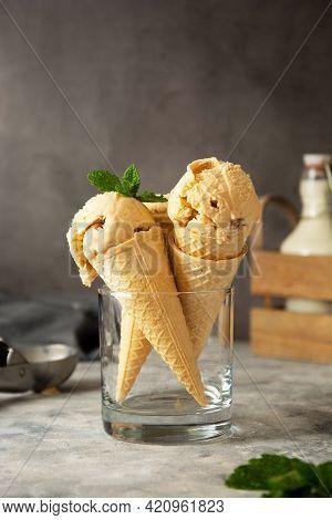 Caramel Ice Cream Scoops With Raisins, In A Waffle Cones On Dark Background. Summer Ice-cream Treat.