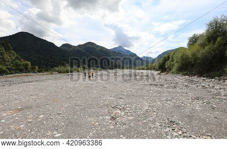 Family Of Four Walking In The Middle Of The Dry River Bed Due To The Karst Phenomenon