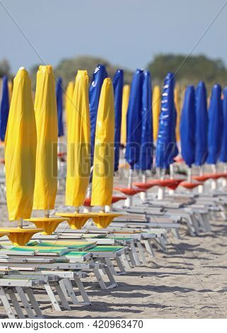 Beach With Closed Yellow And Blue Umbrellas With No One On The Deck Chairs Due To The Lockdown In Th