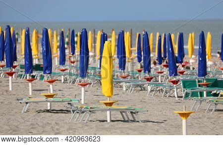 Beach With Closed Umbrellas With No One On The Deck Chairs Due To The Lockdown