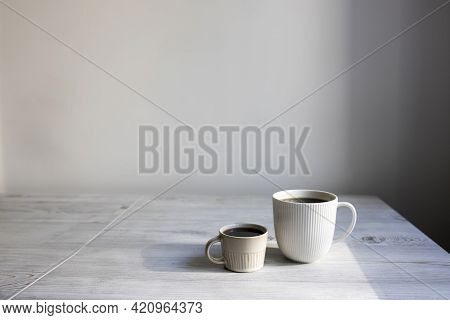 Minimalistic Scandinavian Style. Two Cups Of Coffee Of Different Sizes For Two On On The Table.