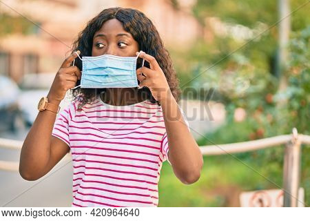 Young african american girl putting on protective medical mask standing at the park.