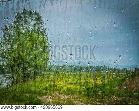 Colorful view of french countryside through the window glass of the car covered by raindrops.