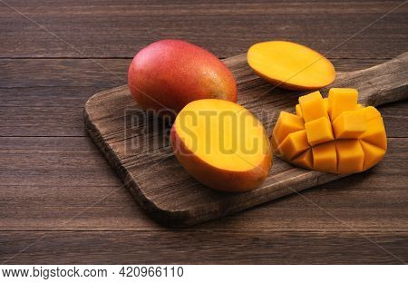 Mango. Fresh Mango Fruit With Leaves Over Dark Wooden Table Background.