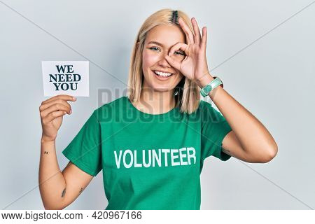 Beautiful blonde woman wearing volunteer t shirt showing we need you banner smiling happy doing ok sign with hand on eye looking through fingers